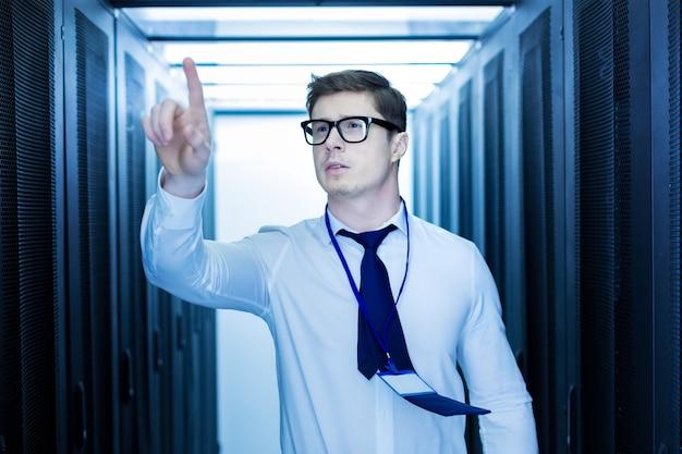 Trabajo interesante. hombre guapo inspirado trabajando en un centro de datos y apuntando con su dedo