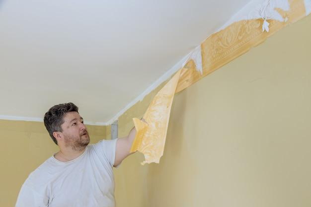 El trabajo manual con la mano del trabajador raspador raspando papel tapiz antiguo en la pared con preparación para pintar una habitación