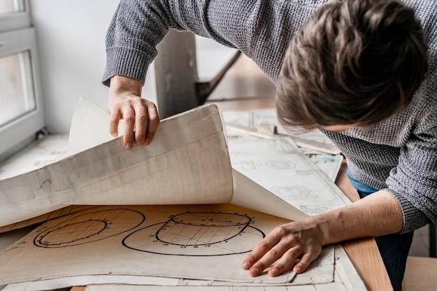 Trabajo masculino joven con arquitectura de gráficos en papel