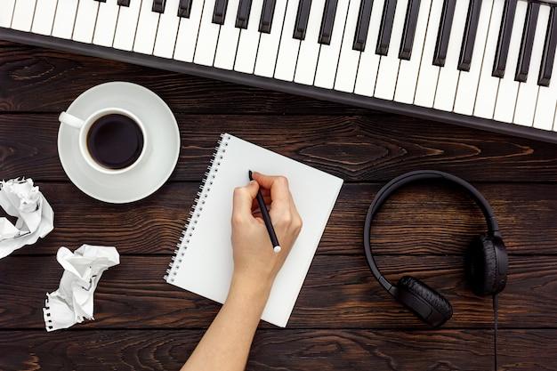 Trabajo de músico con sintetizador, nota y auriculares.