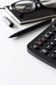 Trabajo de oficina con espacio de texto, libro negro, gafas y calculadora en mesa blanca