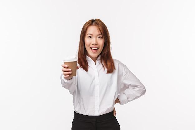 Trabajo de oficina, personas y concepto de negocio. mujer asiática alegre y energizada sugiere beber, darle una taza de café y sonreír, decir aquí está, tratando a un amigo en el café, de pie en la pared blanca