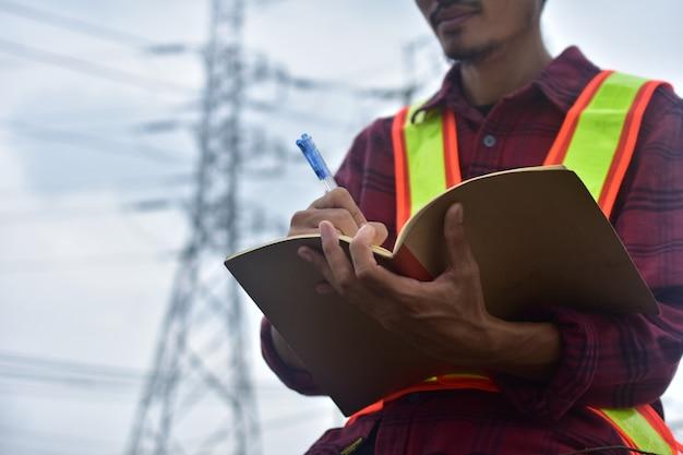 Trabajo de plan de registro de ingeniero en el trabajo en cuaderno y consultor de sombrero de seguridad de constructor de mano para ocupación con papel de nota y escritura
