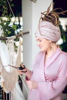Trabajo en progreso. mujer en un sombrero de corte de hilo mientras teje macramé
