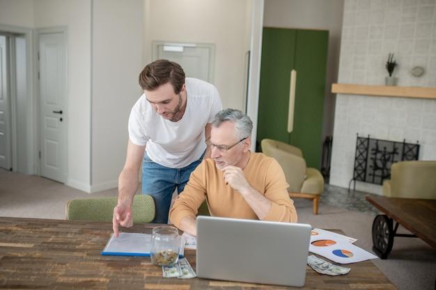Trabajo de proyecto. dos hombres trabajando juntos en un proyecto y mirando interesados