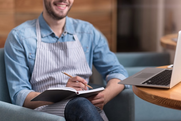 Trabajo relajado. agradable joven guapo sonriendo y tomando notas mientras usa la computadora portátil.