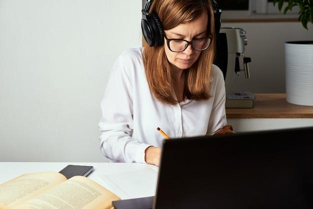 Trabajo remoto. curso online, educación a distancia y concepto de e-learning. mujer en auriculares escuchar curso de audio en el portátil