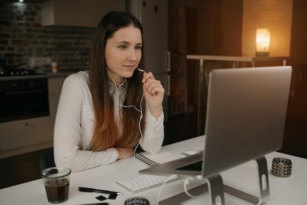 Trabajo remoto. una mujer caucásica con auriculares trabajando remotamente en línea en su computadora portátil. una chica con una camisa blanca discutiendo negocios con sus colegas a través de una videollamada en su acogedor hogar.