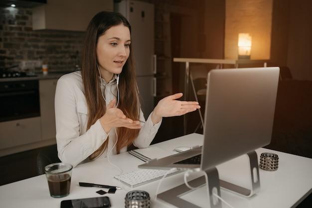 Trabajo remoto. una mujer caucásica con auriculares trabajando remotamente en línea en su computadora portátil. una chica que habla activamente de negocios con sus colegas a través de una videollamada en su acogedor hogar.