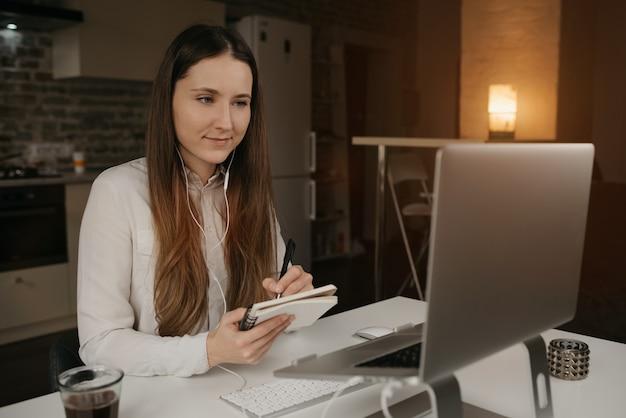 Trabajo remoto. una mujer caucásica con auriculares trabajando remotamente en su computadora portátil. una chica con una camisa blanca haciendo notas durante una reunión de negocios en línea en su acogedor lugar de trabajo en casa.