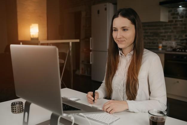 Trabajo remoto. una mujer caucásica con auriculares trabajando remotamente en su computadora portátil. una chica morena con una camisa blanca haciendo notas durante una sesión informativa de negocios en línea en su acogedor lugar de trabajo en casa.