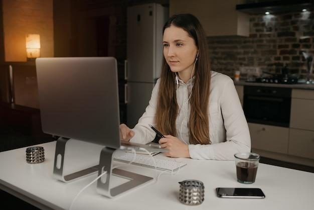 Trabajo remoto. una mujer morena caucásica con auriculares trabajando remotamente en línea en su computadora portátil. una chica con una camisa blanca haciendo una videollamada a sus socios comerciales en su acogedor lugar de trabajo en casa.