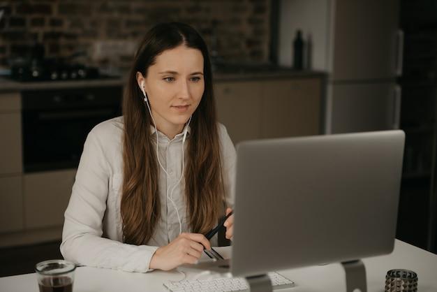 Trabajo remoto. una mujer morena caucásica con auriculares trabajando remotamente en su computadora portátil. una chica con una camisa blanca haciendo una videollamada a sus socios comerciales en el lugar de trabajo de su casa.