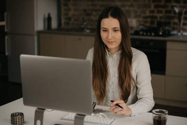 Trabajo remoto. una mujer morena caucásica con auriculares trabajando remotamente en su computadora portátil. una dama en una camisa blanca haciendo negocios en su lugar de trabajo en casa.