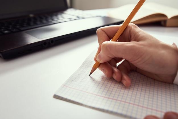 Trabajo remoto. la mujer toma notas en el cuaderno y usa la computadora portátil para estudiar. concepto de educación a distancia y e-learning