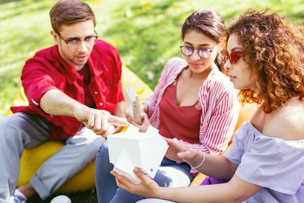 Trabajo serio. hombre serio concentrado sentado al aire libre con sus compañeros de trabajo y discutiendo su proyecto