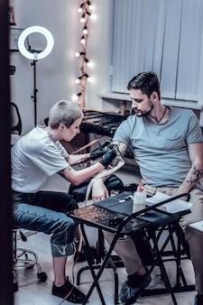 Trabajo de tatuaje inacabado. la atenta maestra y su obediente cliente pasan una sesión en el salón de tatuajes mientras terminan el último trabajo