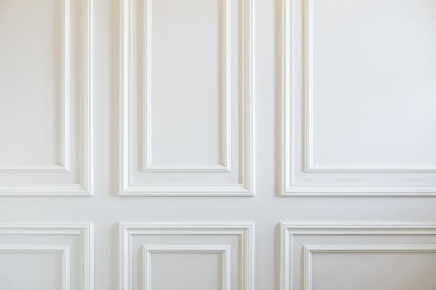 Trabajos de acabado: fragmento de paredes blancas clásicas con paneles de pared instalados, decorados con molduras. fondo