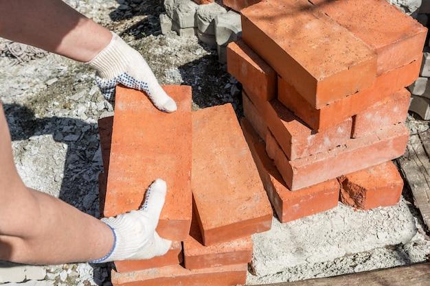 Trabajos de construcción en una casa particular un albañil toma ladrillos de una pila para construir una pared