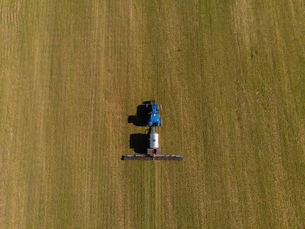 Tractor aplicando fertilizantes minerales líquidos al suelo en trigo de invierno