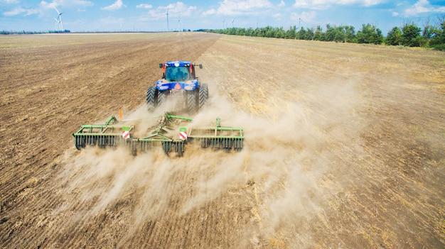 Un tractor arando y sembrando en el campo