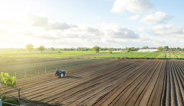 Un tractor cabalga sobre un campo agrícola granjero en un tractor con fresadora afloja muele y mezcla el suelo