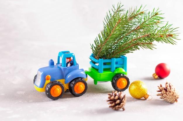 Tractor de juguete que lleva un árbol de navidad con rama de abeto, cono de abeto. espacio para texto. cerca de la foto.
