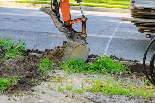 El tractor municipal urbano con cuchara es cavar la alcantarilla en movimientos de tierra.