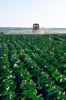 El tractor rocía productos químicos y pesticidas a un campo agrícola