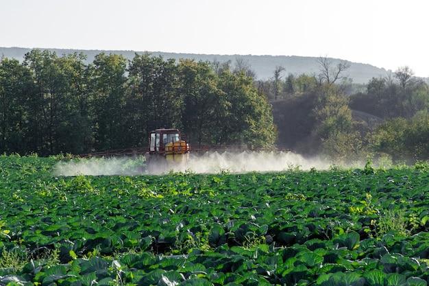 El tractor rocía productos químicos y pesticidas a las hortalizas de un campo de granjas