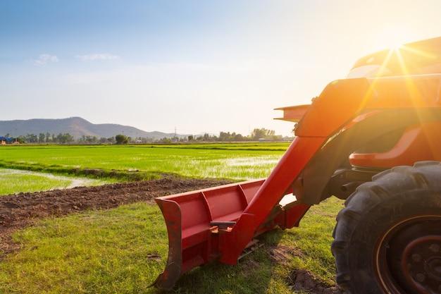 Tractor rojo en el campo agrícola en día soleado de verano