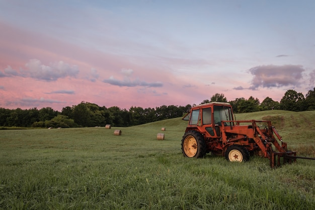 Tractor rojo y fardos de heno recién enrollados en una tierra de cultivo al atardecer