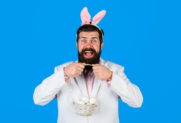 La tradición de la pascua y el símbolo del hombre barbudo en orejas de conejo mantenga la canasta con huevos felices pascuas preparando