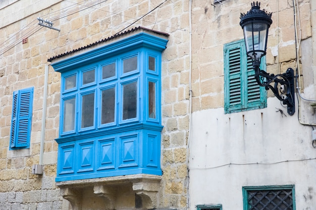 Tradicional, balcón de madera y fachada de piedra, típica de la arquitectura de gozo, malta.