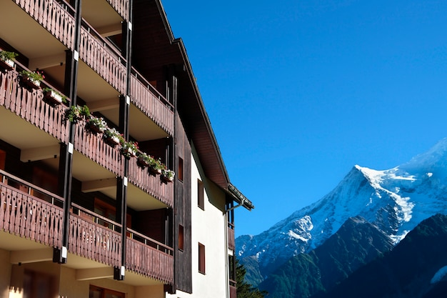 Tradicional hotel de esquí alpino europeo, vista de los alpes en la distancia. copiar espacio en cielo azul.