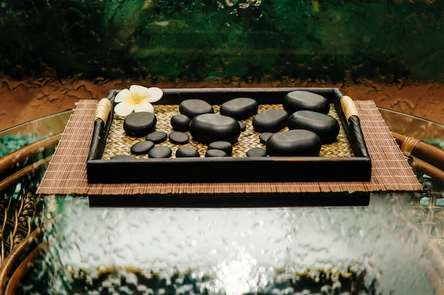 Tradicional tailandesa ceremonia famosa bronce antiguo tetera en bandeja de mimbre con flores de loto y piedras negras.