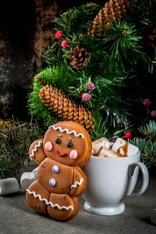 Tradicional trato navideño. chocolate caliente con malvavisco, galleta de hombre de jengibre, ramas de abeto y decoraciones navideñas de navidad copyspace