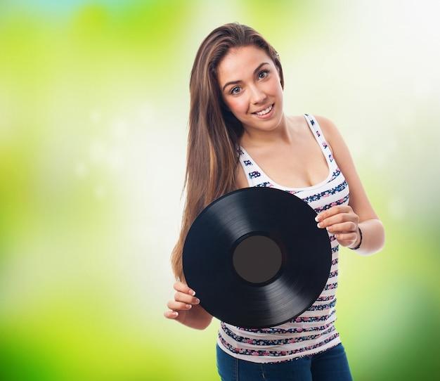 Traducir  mujer sonriendo con un disco de vinilo