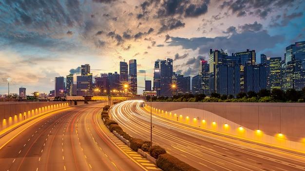 Tráfico de la autopista de la ciudad de singapur con movimiento de la luz del coche en el fondo de rascacielos
