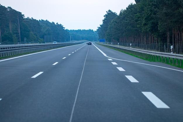 Tráfico de la carretera al atardecer con coches y camiones.