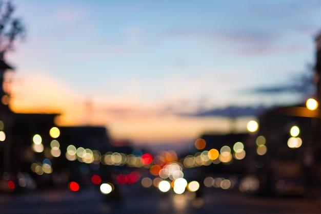 Tráfico desenfocado y luces de la ciudad en la gran calle urbana al atardecer
