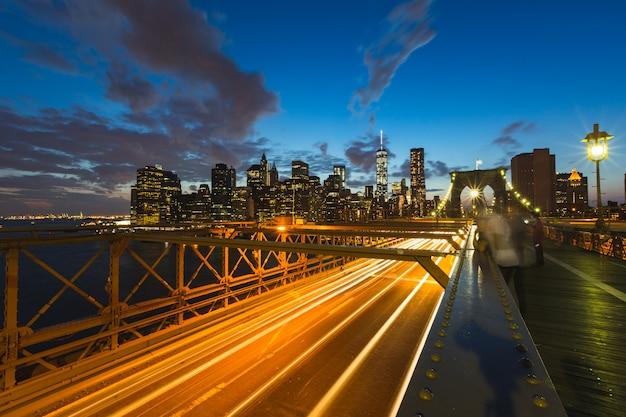 Tráfico en el puente de brooklyn en nueva york al atardecer