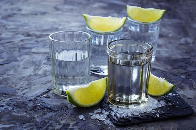 Tragos de tequila plateado mexicano con lima y sal. enfoque selectivo