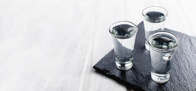 Tragos de vodka en mesa blanca