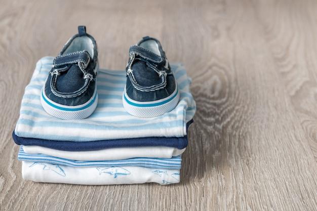 Traje azul y blanco doblado con zapatos sobre fondo de madera gris.