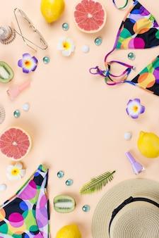 Traje de baño bikini con sombrero de paja, flores y frutas, diseño plano, concepto de verano. destino de playa, moda de verano