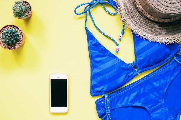 Traje de baño de color azul con smartphone, cactus y sombrero plana puesta sobre fondo amarillo, concepto de vacaciones de verano