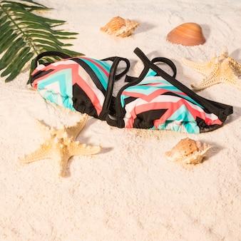 Traje de baño en la playa con hojas y conchas.