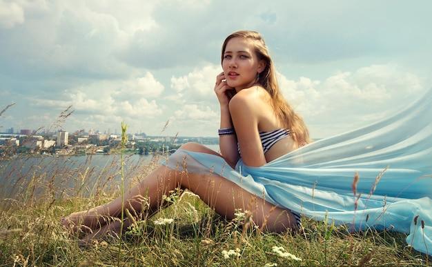 Traje de baño rubio joven hermoso de la mujer en verano