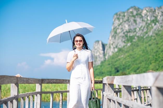 Traje blanco de una mujer caminando en el puente de madera